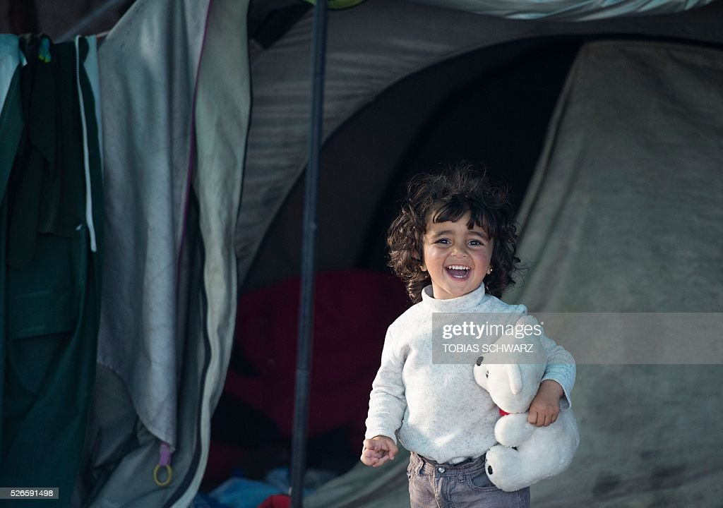 A girl holds her cuddly toy as she stands in a tent at a makeshift camp for migrants and refugees near the village of Idomeni not far from the Greek-Macedonian border on April 30, 2016. Some 54,000 people, many of them fleeing the war in Syria, have been stranded on Greek territory since the closure of the migrant route through the Balkans in February. / AFP / TOBIAS