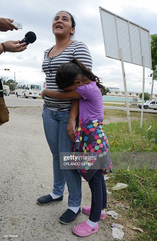 A girl holds her mother tight as she speaks to the press upon arriving in San Pedro Sula, about 260 km north of Tegucigalpa, on July 14, 2014 after being deported from the United States. A first group of 120 deportees from Honduras, El Salvador and Guatemala who had crossed into the United States illegally were repatriated by plane to their countries -- most of them unaccompanied youths. US authorities have detained some 57,000 unaccompanied minors since October, twice the number from the same period a year ago, seeking to illegally cross into the US from Mexico. AFP PHOTO/Orlando SIERRA