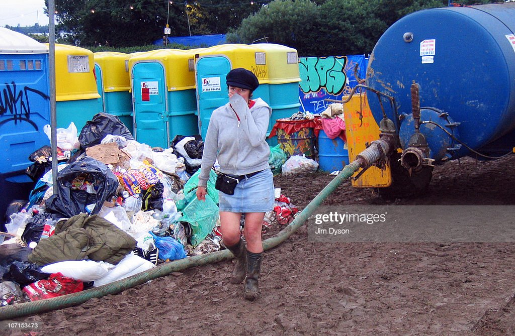 A girl holds her nose from the stench of rubbish and toilets in the mud, after a thunderous night of heavy rain during the Glastonbury Music Festival held at Worthy Farm on June 24, 2005 in Glastonbury, England.