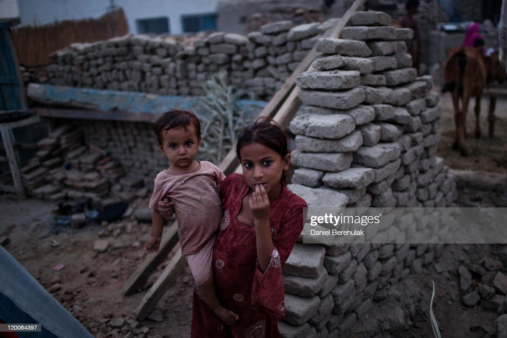 A girl holds her younger brother on the site of their home, destroyed by last year's floods, next to their temporary accomodation one year on, on July 29, 2011 in the village of Basti Jagwala Shoki, near Muzaffargarh, Pakistan. A year ago, monsoon rains caused flooding which ravaged Pakistan causing the worst natural disaster since its inception in 1947. Flood waters submerged a fifth of the countryside, equivalent to the size of England, affecting over 20 million people, displacing over 4 million and killing 2000. Millions lost their homes, farms and livelihoods. But the crisis still continues, as hundreds of thousands of people still remain homeless. Malnutrition rates in some districts on a par with some African countries. Some 800,000 families lack permanent shelter and more than a million people require food aid, according to Oxfam. Families are struggling to rebuild their homes, as the cost of bricks has doubled in most areas and quadrupled in others. For many, the impact of the disaster will continue to be felt for years to come. The residents of Bast Jagwala Shoki are having to rebuild their homes from scratch, which were completely destroyed by the floods. Many families are building their homes in stages, using a combination of the remains of whatever materials were not washed away and new materials. The residents have not had any assistance and are having to use what meagre savings they make on a monthly basis to build their homes. Many residents make an average of $3USD a day.