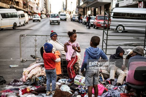 A girl holds on to a dress as she stands with a family of former residents of the Fattis Mansion who sit amid their belongings and were evicted the...
