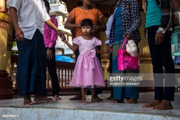A girl holds on to her father's hand as she and other members of her family wait to board a boat that willd take them to the Kyauktan Ye Le Pagoda a...