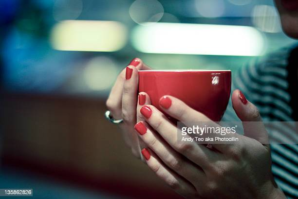 Girl holds red coffee cup