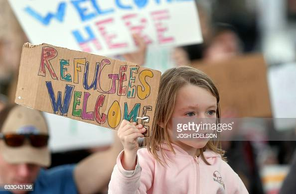 A girl holds up a sign as protesters shout at San Francisco International Airport in San Francisco California on January 29 2017 US President Donald...