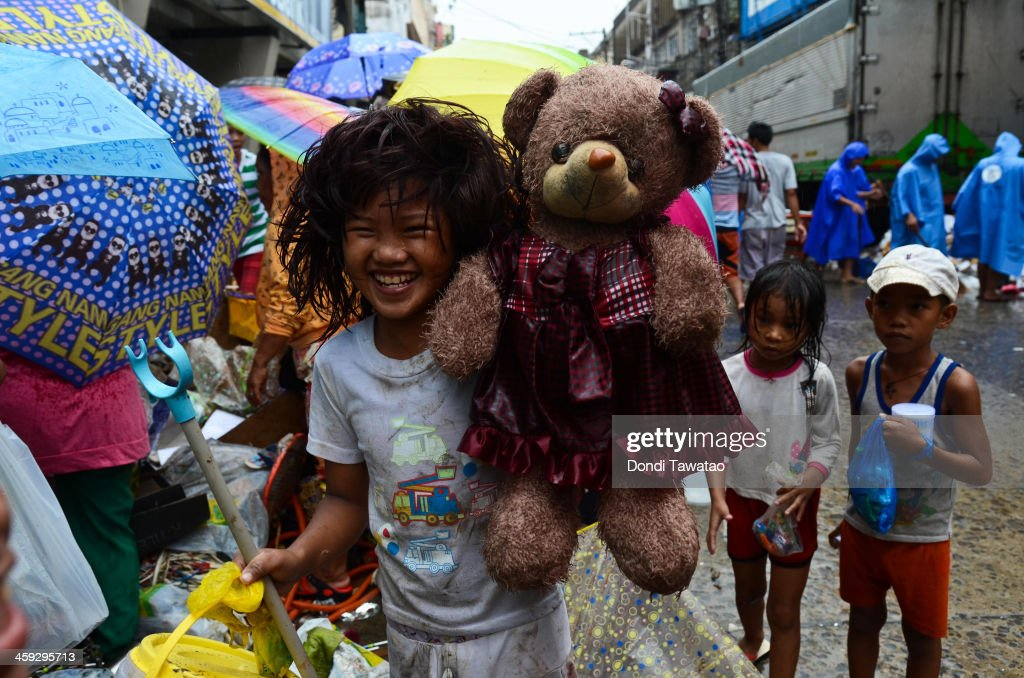 TACLOBAN, LEYTE, PHILIPPINES - DECEMBER 25: A girl holds up a teddy bear she found among piles of debris discarded by a grocery store on Christmas day on December 25, 2013 in Tacloban, Leyte, Philippines. Haiyan has been described as one of the most powerful typhoons ever to hit land, leaving thousands dead and hundreds of thousands homeless. Countries all over the world have pledged relief aid to help support those affected by the typhoon. With Christianity being the predominant religion in Philippines, the people of Tacloban will try to find a way to celebrate Christmas despite the incredibly difficult circumstances.