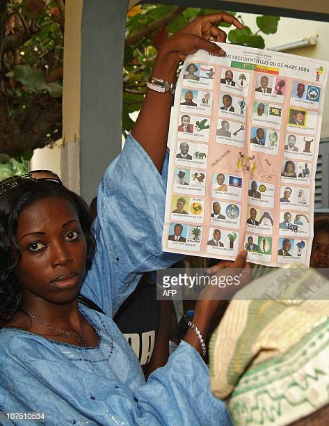 A girl holds up an electoral voting pamphlet 05 March 2006 at a polling station in Akpakpa The small west African republic of Benin went to the polls...