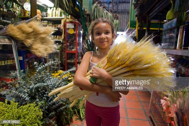A girl holds wheat ears used for New Year's rituals at a market in Medellin Colombia on December 30 2014 In great part of Latin America New Year is...