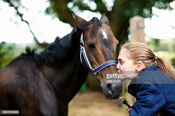 Girl horseback rider kissing horse