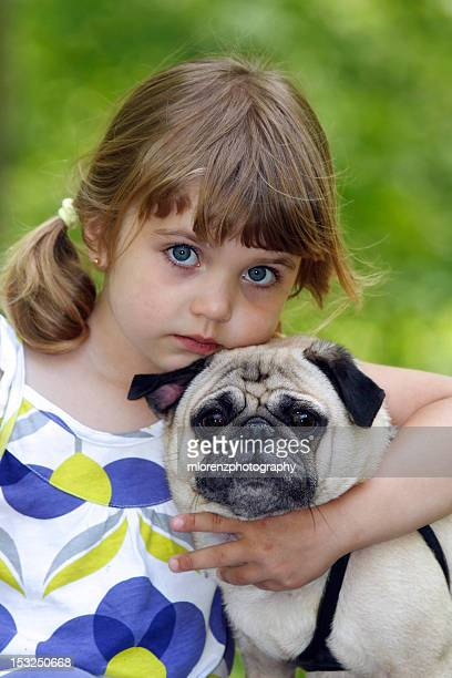 Girl huggging pug puppy