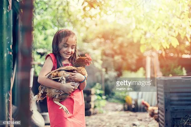 Girl hugging a hen