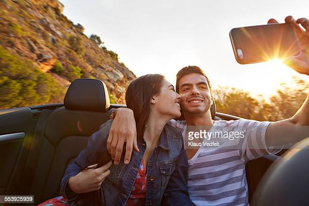 Girl hugging boyfriend while making selfie in car