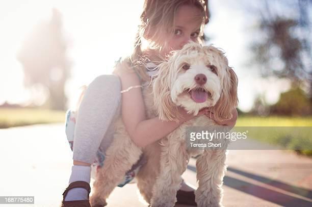 Girl Hugging Cockapoo Dog