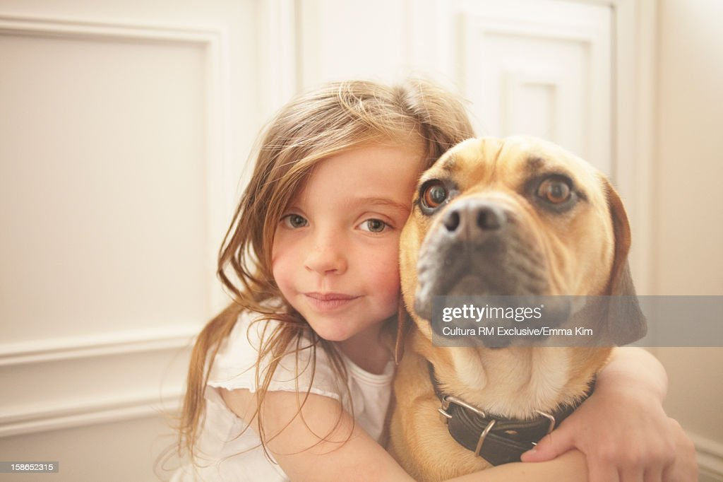 Girl hugging dog indoors : Stock Photo