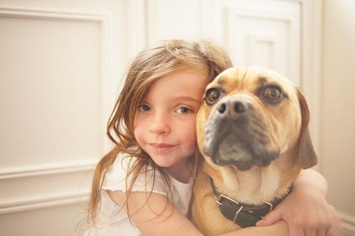Girl hugging dog indoors