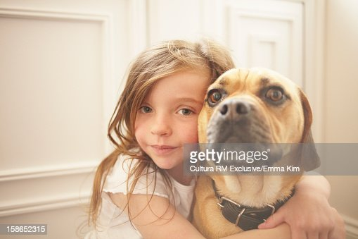 Girl hugging dog indoors : Stock Photo