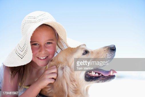 Girl hugging dog on beach : Stock Photo
