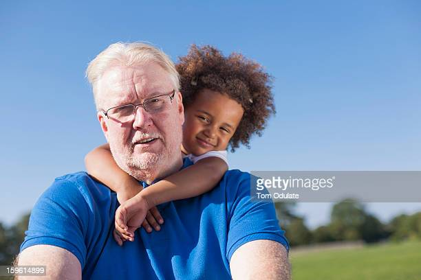 Girl hugging grandfather outdoors