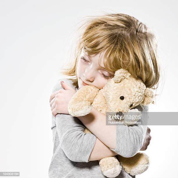 girl hugging her teddy bear