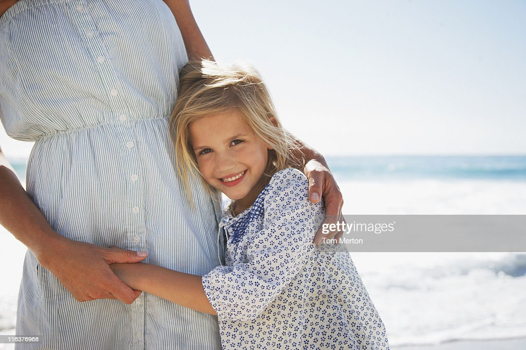 Girl hugging mother on beach : Stock Photo