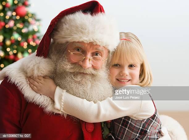 Girl (4-5) hugging Santa Claus, portrait, close-up