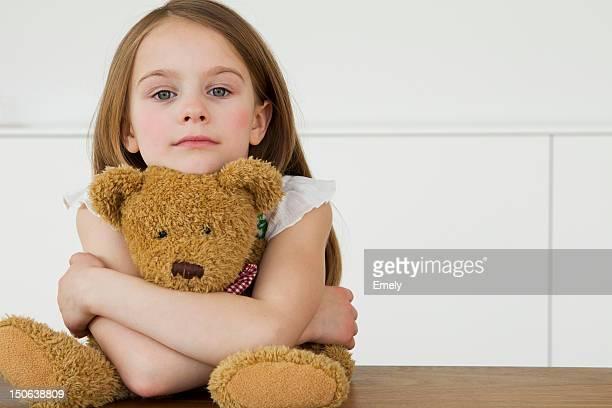 Girl hugging teddy bear at table