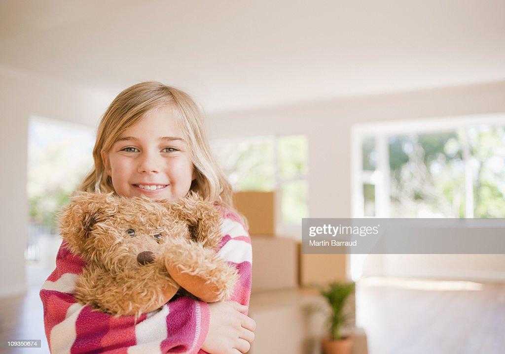 Girl hugging teddy bear in new house : Stock Photo