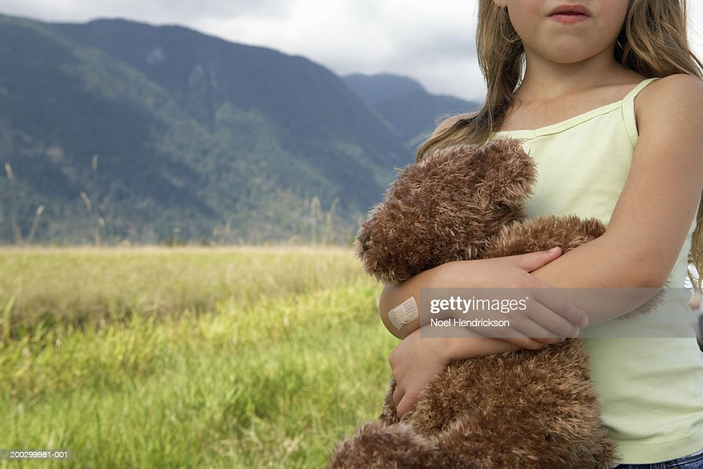 Girl (5-7 years) hugging teddy bear outdoors, close-up : Stock Photo