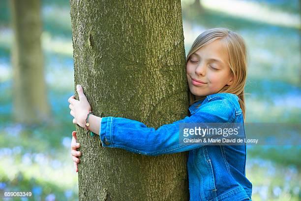 Girl hugging tree in bluebell forest, Hallerbos, Brussels, Belgium