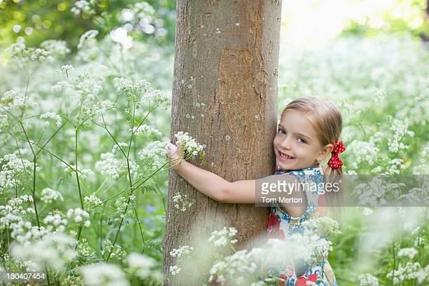 Girl hugging tree in field of flowers