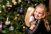 Girl hugs doll at Christmas