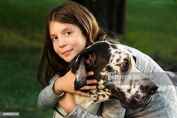 Girl hugs her big strong buddy Great Dane