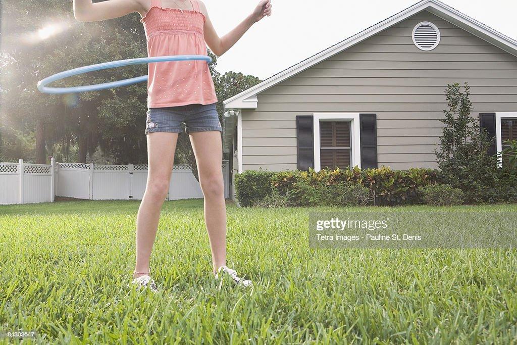 Girl hula hooping in backyard