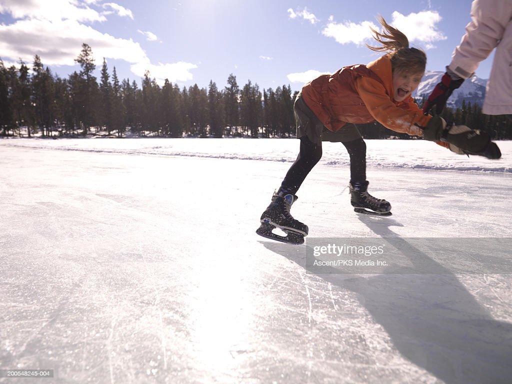 Girl (10-11) ice skating on frozen pond, screaming : Stock Photo
