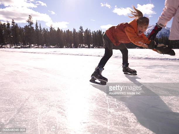Girl (10-11) ice skating on frozen pond, screaming