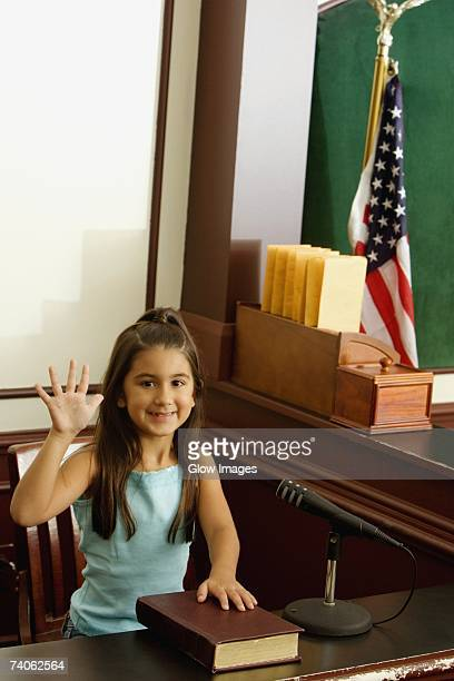 Girl imitating a witness taking oath in a courthouse