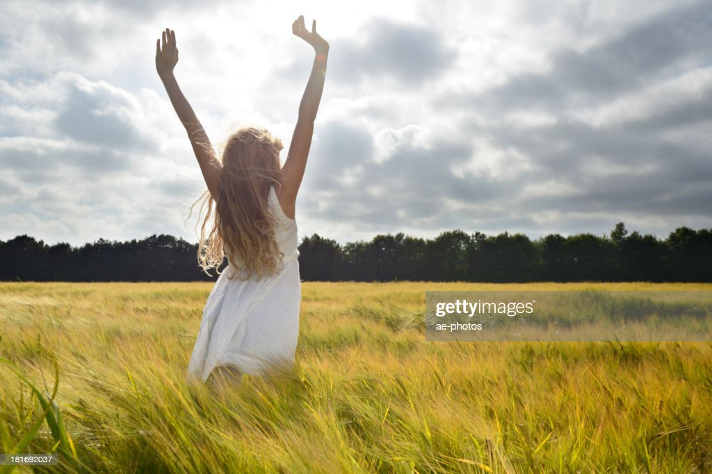 Girl in a grainfield in summer, arms outstretched