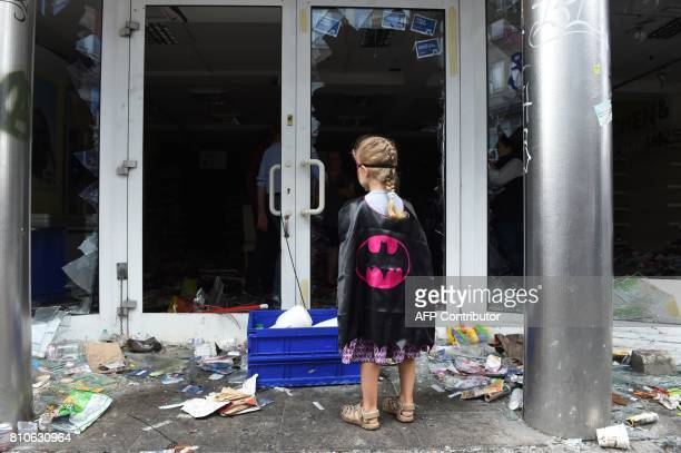A girl in a Batman costume stands in front of a looted Budnikowsky drugstore after riots in Hamburg's Schanzenviertel district on July 8 2017 in...