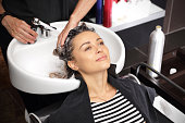a hairdresser's hands wash the head girl in a beauty salon