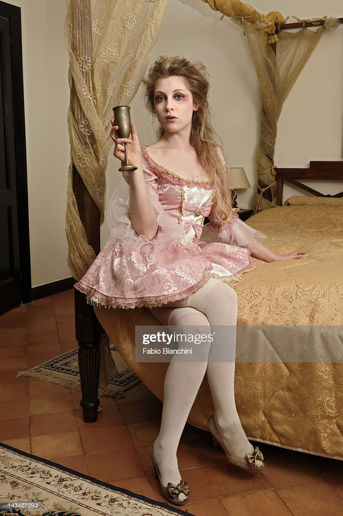 Girl in a bedroom drinking from a chalice : Stock Photo