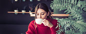 A beautiful girl in a red knitted sweater drinks tea and reads a book in a cozy cafe, the concept of pleasant leisure and communication