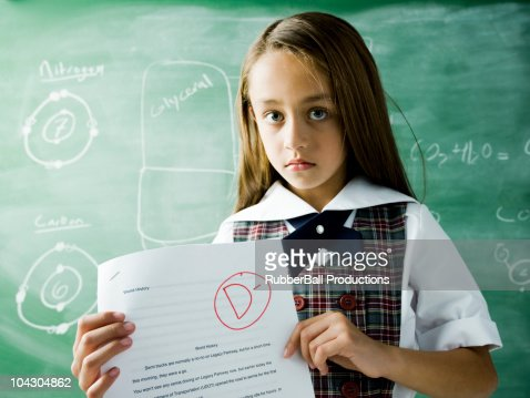 girl in a classroom holding a paper with a d minus grade : Stock Photo