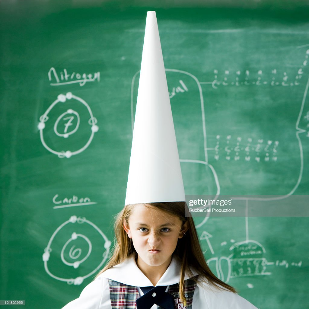 girl in a classroom standing in front of a chalkboard wearing a dunce cap
