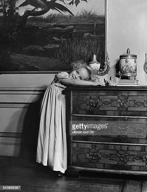 Girl in a festive dress leaning on a commode ca 1937 Photographer Hedda Walther Published by 'Das Blatt der Hausfrau' 1937Vintage property of...
