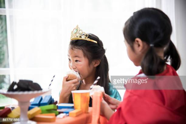 A girl in a princess costume that eats a cupcake.