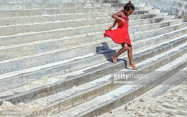 Girl in a red dress running down steps