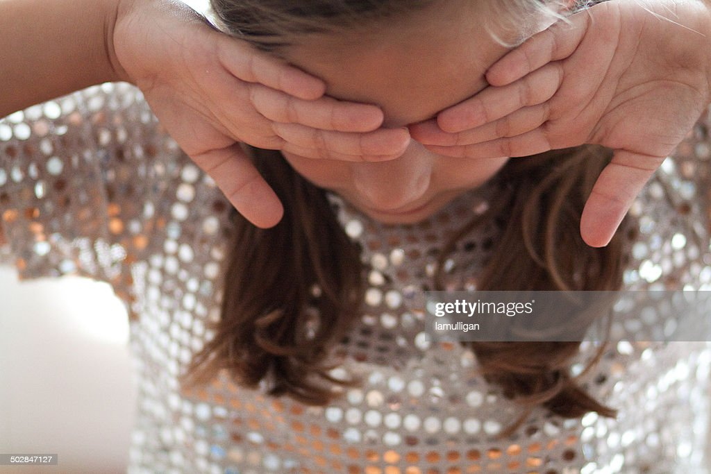 Girl (6-7) covering eyes with backs of hands