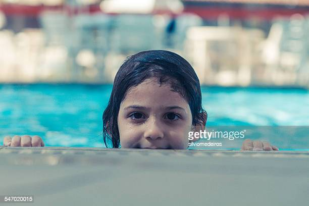 Girl in a swimming pool looking over edge