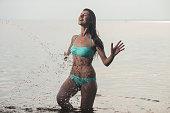 Beautiful girl in a swimsuit posing in the sea, having fun and splashing in the water