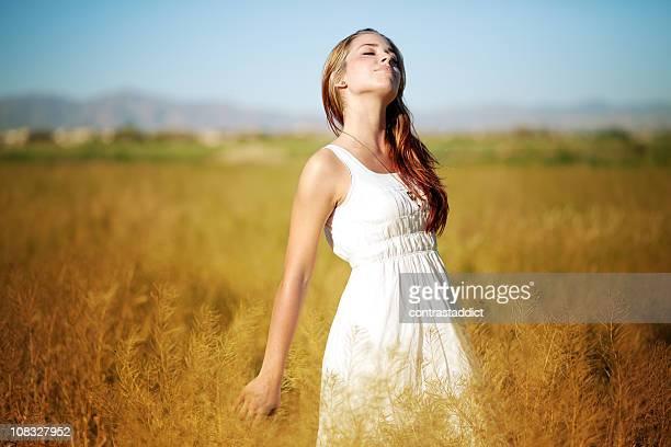 Ragazza in un abito bianco cammina attraverso il campo di grano.
