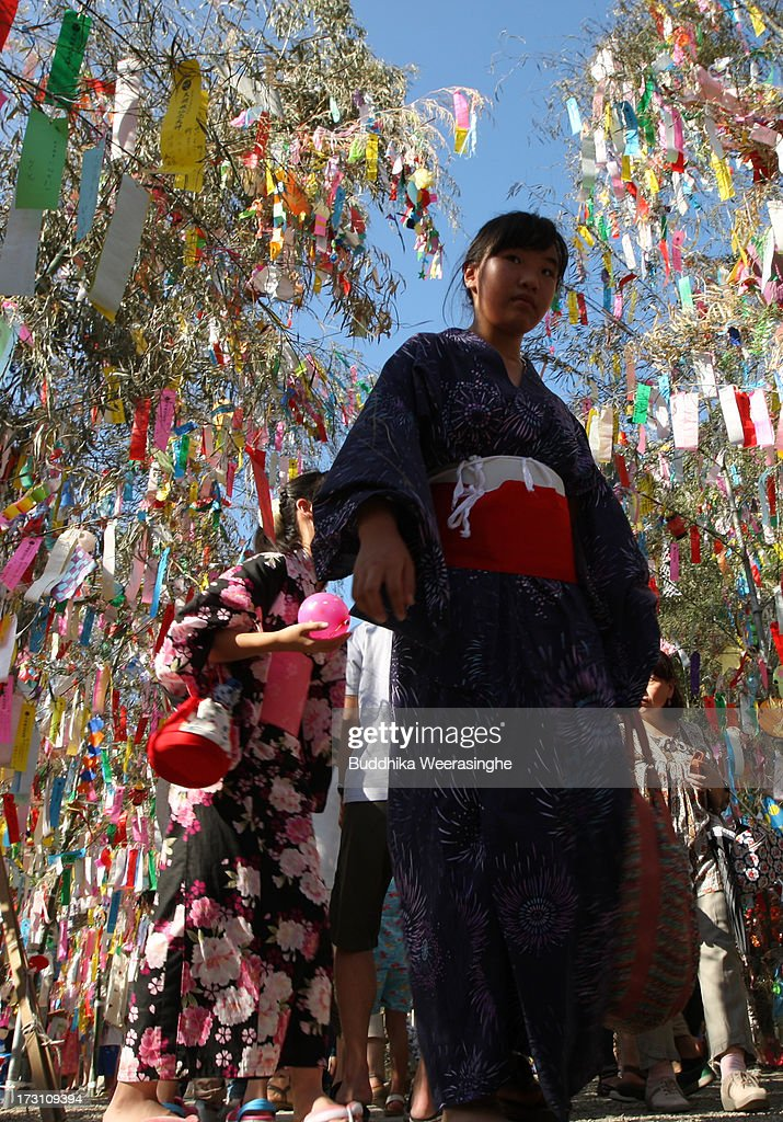 A girl in a Yukata, an informal summer kimono, walks under the colorful paper strip decorations hung from bamboo branches during the Tanabata festival at the Hatamono shrine on July 7, 2013 in Osaka, Japan. Tanabata is a Japanese star festival in which people wear traditional ''yukata'' robes and write their wishes on strips of paper to hang on bamboo trees.